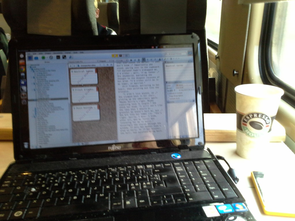 Laptop with paper mug of coffee